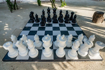 Outdoor Chess Game at Big Chequer Board. Super big size of black and white chess game pieces,
