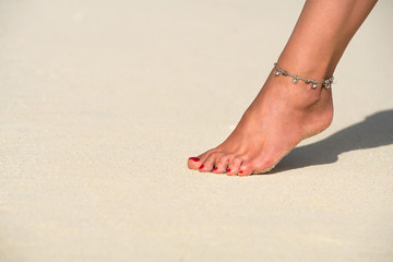 Close-up of female foot in the sand on the tropical beach. Vacation holidays.