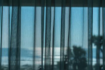 Mesh curtain drawn across window of hotel room overlooking the ocean