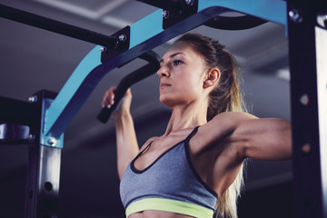 Front profile of young woman doing chin ups at fitness centre