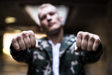 Blurred stylish male showing two fists to camera