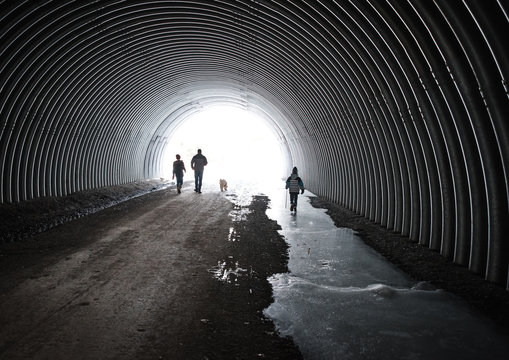 Man, two children and dog walking through an icy metal tunnel.