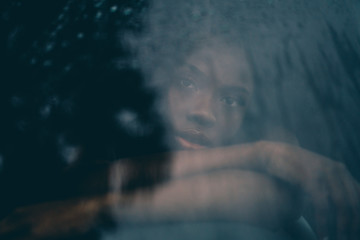 Portrait African woman behind a window wet from the rain.