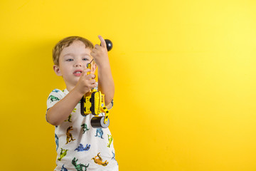 adorable small three years old boy with cute face expression playing with his toy Wall mural