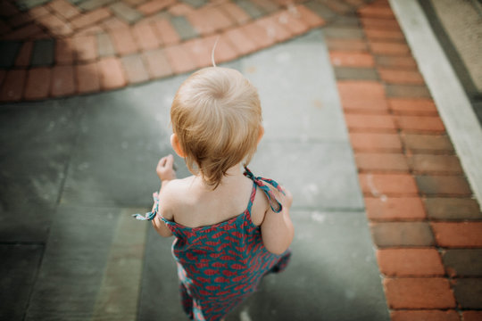 baby walking on slate and brick path in the summer, shot from behind