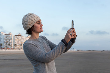 Portrait of a woman taking a selfie with her smartphone on the beach