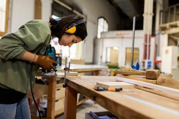 Female carpenter using cutting machine at workshop