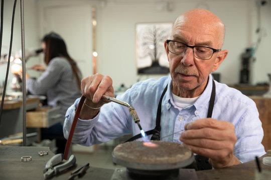 Senior goldsmith working in workshop