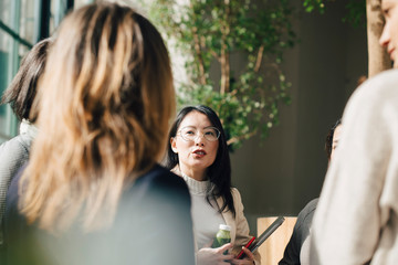 Female professional discussing with coworkers in meeting at conference event