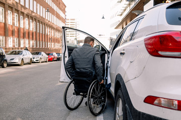 Rear view of man in wheelchair getting into car
