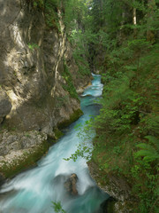 VERTICAL: Beautiful view of a turquoise colored stream rushing through the woods