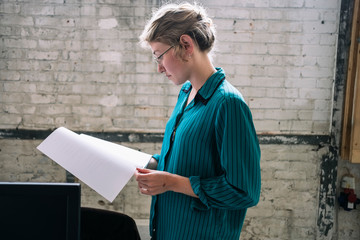Side view of businesswoman reading documents in office