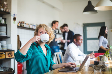 Businesswoman drinking coffee while working in office