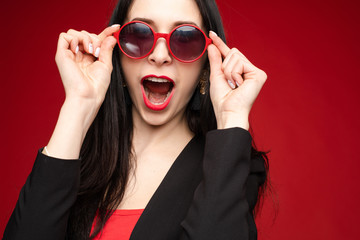 Studio headshot of funny cheerful and positive brunette woman with red lips showing or expressing happiness and excitement in fashionable red round sunglasses. She is posing against red background.