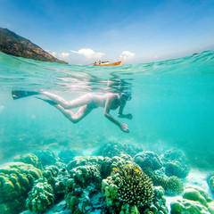 woman snorkeling in clear tropical waters, split image of underwater and longtail boat on surface - active exotic holiday