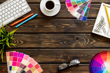 Work space of designer with instruments, pallet, keyboard, glasses and coffee wooden background top view space for text
