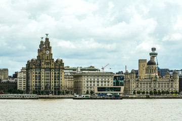 Liverpool seafront view from ferry in a summer cloudy day with the royal liver building imposing
