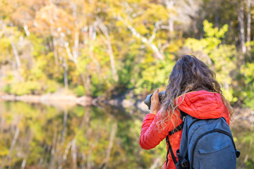 Young woman photographer with backpack and camera taking photo, photographing Great Falls autumn foliage view with river reflection in Maryland