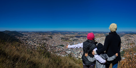 Panoramic photo with mother with daughter and son  on top of the mountain watching the city Poços de Caldas - Minas Gerais / Brazil - below.