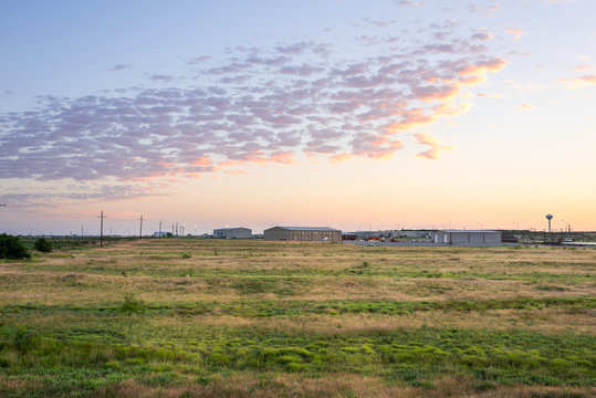 Colorful sunrise in Snyder Texas with industrial building, warehouses or storehouses and factory by farm field with electricity pylons
