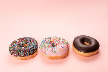 Three tasty doughnuts on pink background.