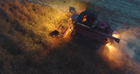 Wall Mural - Aerial view above lights of combine harvester in a field at sunset. Tractors and farm machines harvesting.