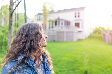 Young woman smiling homeowner in Northern Virginia, Fairfax county residential neighborhood in spring or summer by house backyard