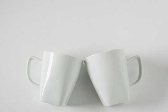 White coffee mugs on white background clinking in cheers with empty copy space