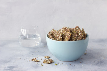 Delicious healthy multigrain gluten-free crackers, ketogenic, from chia seeds, flax, sesame and ground pumpkin seeds in a ceramic bowl on a gray background, horizontal