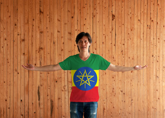 Man wearing Ethiopia flag color shirt and standing with arms wide open on the wooden wall background.