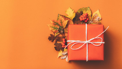 Autumn season decor. Top view of handmade paper gift box adorned with fall leaves. Orange background. Copy space.