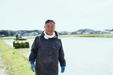 Portrait of smiling farmer standing in field
