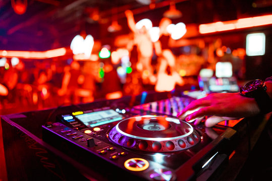 Dj mixing outdoor at beach party festival with crowd of people in background - Summer nightlife view of disco club outside - Soft focus on hand - Fun ,youth,entertainment and fest concept