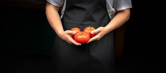 Personne qui porte des tomates rouge dans les mains