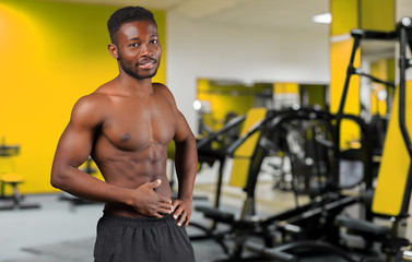Cheerful handsome African sportsman with muscular strong body smiling to the camera