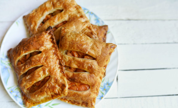 Puff pastry apple pastry turnovers for dessert on a white wooden table with copy space