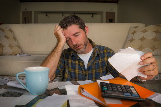 frustrated man at home living room couch doing domestic accounting overwhelmed and worried suffering financial problem going over taxes and payments paperwork
