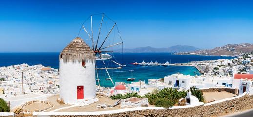 Blick über die Stadt und den Hafen der Insel Mykonos im Sommer mit traditioneller Windmühle und weißgewaschenen Häusern, Kykladen, Griechenland