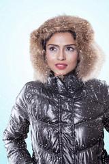 Pensive woman wearing winter jacket on studio
