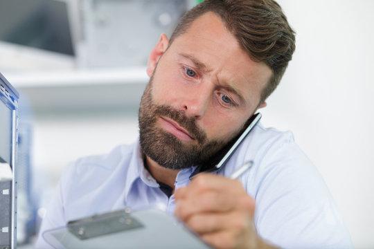 businessman holding mobile phone between ear and shoulder
