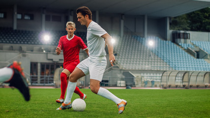 Professional Soccer Player Leads with a Ball, Masterfully Dribbling and Bypassing Sliding Tackles of His Opponents. Two Professional Football Teams Playing. Low Angle Shot.