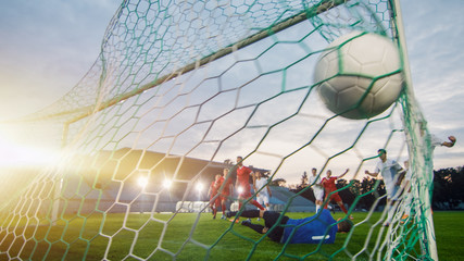 On Soccer Championship Goalkeeper Tries to Defend Goals but Jumps and Fails to Catch the Ball. Shot from Behind the Net with the Ball in it. Stadium Shot with Warm Sunlight Flare in the Background.