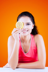 Smiling woman covering her one eye with orange