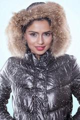 Smiling woman wearing winter jacket on studio