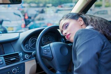 Tired businesswoman falling asleep in a car