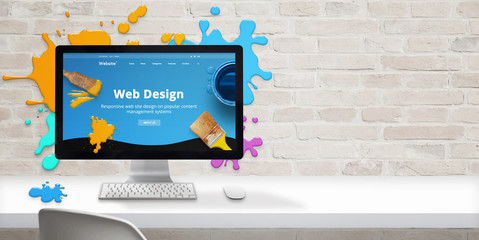 Web design studio concept with modern web site teme and web design text on computer display surrounded by color drops. Free space beside on brick wall for text.