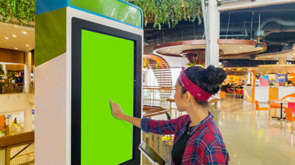 Woman touches a screen of self-ordering kiosk