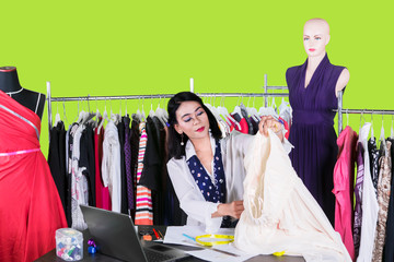Young fashion designer holds a fabric on studio