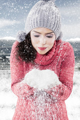 Young woman blowing snow from her hands