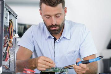 a computer specialist repairing pc Wall mural